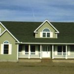 a custom green house with green shingles, white accents, white front porch and white shutters