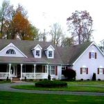 a custom two story home with grey siding, red shutters and a white front porch and circular driveway