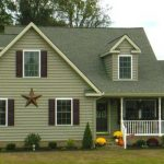 a custom home with green siding, green shingles and a large gold star on the side