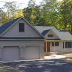 a custom home with two car garage, cream siding with grey roof