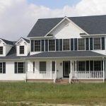 a two story house with grey roof, white siding and front porch