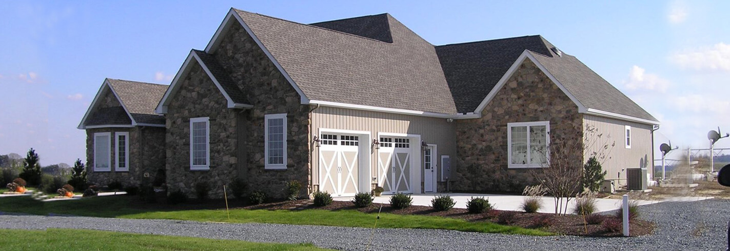 a custom home with stone siding, barn style garage doors and white accents with a grey roof and stone drive